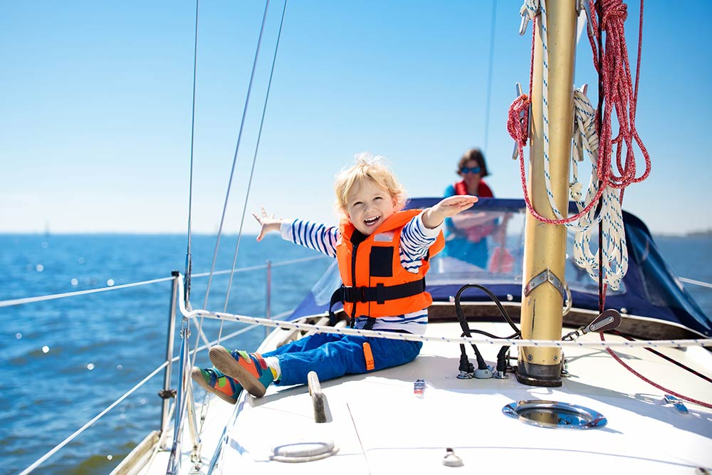 Cute kid on sail boat wearing life jacket